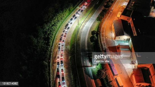 Night-time aerial view of the car waiting for the vaccine before entering the vaccination centre in the Valmontone car park on May 15, 2021 in Rome,...