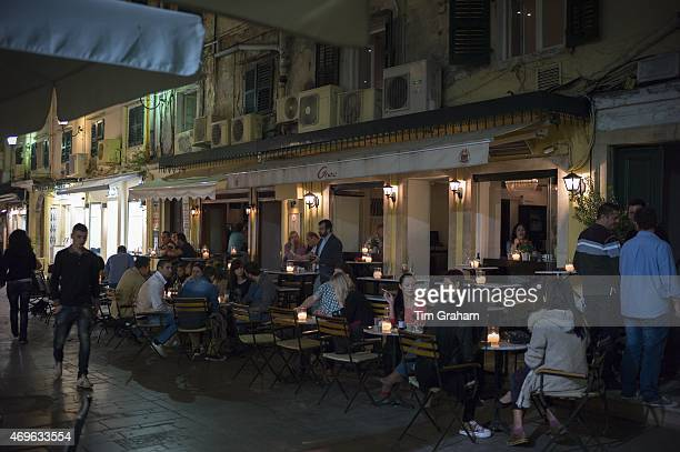 Nighttime cafe society street scene local people and tourists at pavement cafe bar restaurant in Kerkyra Corfu Greece