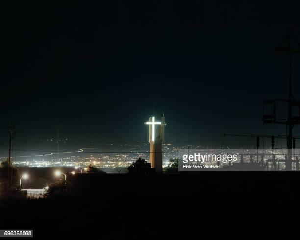 nighttime cityscape of illuminated neon cross on steeple of church