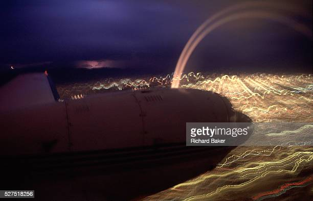 A nighttime exposure during the flight over a city in rural Arizona whose lights are blurred underneath the twinpropeller powered aircraft an air...