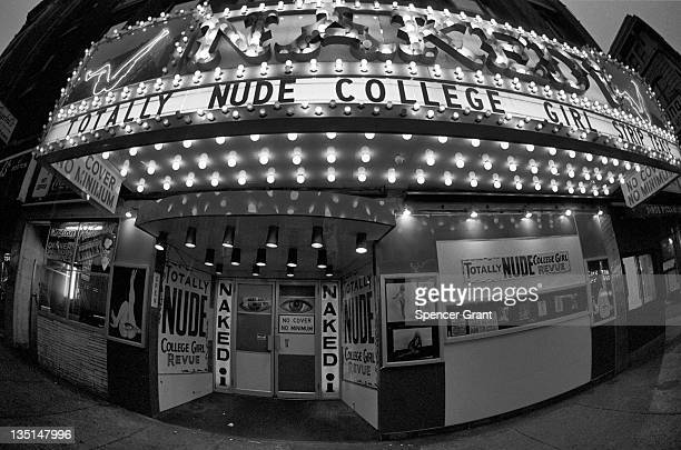 Nighttime exterior view of the entrance to the 'Naked I' strip club on Washington street in Boston's 'Combat Zone' 1974 Signs for the theater...