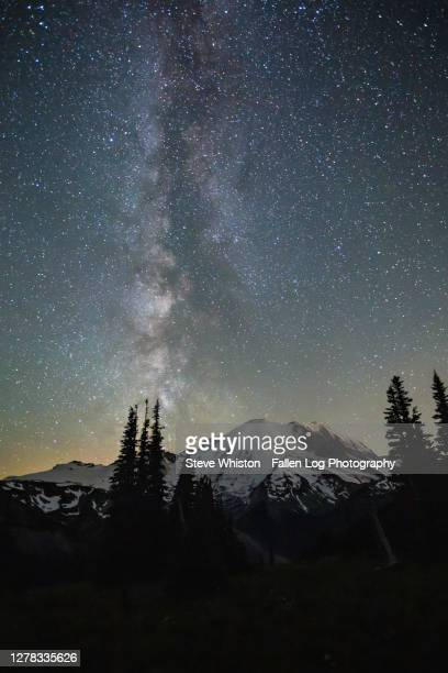 nighttime hikers climb in the distance with milky way over mt rainier - カスケード山脈 ストックフォトと画像