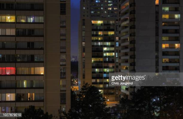 nighttime in a group of residential buildings - fensterfront stock-fotos und bilder