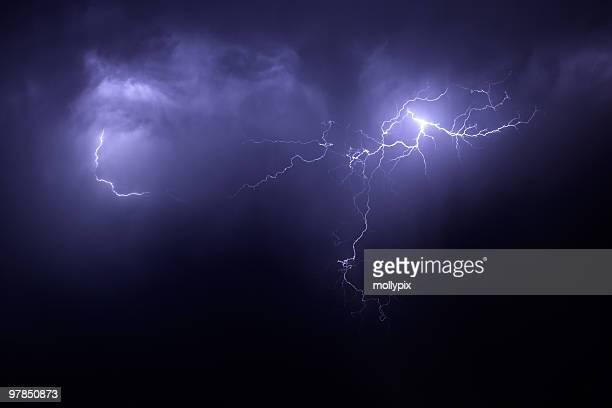 Nighttime lightening storm with streaks across purple sky