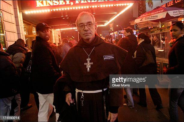 A nighttime portrait of a Friar standing in front of an illuminated movie theater marque Times Square New York December 11 2004