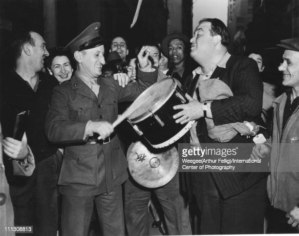 Nighttime portrait of a group of people among them a man in uniform who plays a drum held by a second man in a pinstripe jacket who celebrate VE Day...