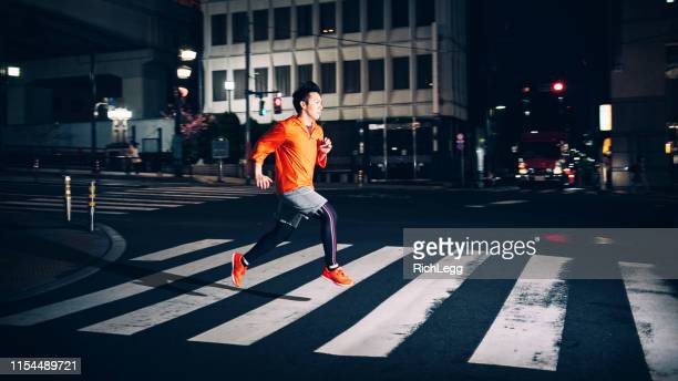 nighttime running in tokyo japan - zebra crossing stock pictures, royalty-free photos & images