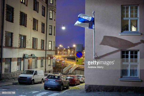 Night-time street scene in Helsinki with Finnish flag on building