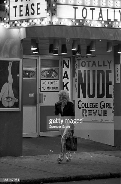 Nighttime view of a blonde woman casts a glance at the doorway as she walks past the entrance to the 'Naked I' strip club on Washington street in...