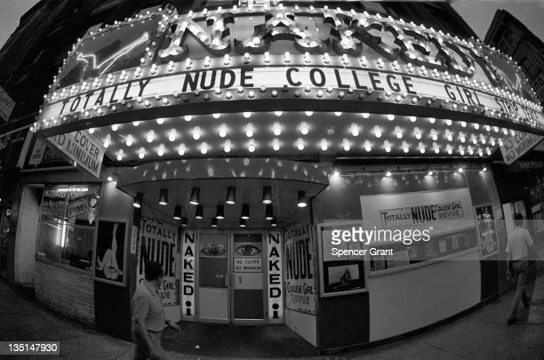 Nighttime view of a male passerby casting a glance at the doorway to the 'Naked I' strip club as he walks past the entrance on Washington street in...