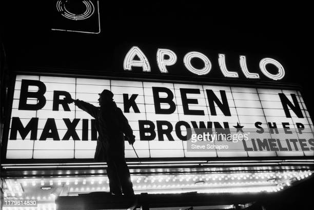 Nighttime view of a man as he changes the letters on the Apollo Theater marquee, New York, New York, 1961. The new sign, though incomplete, will...