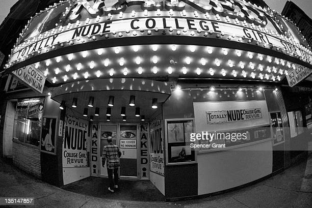 Nighttime view of a man entering the 'Naked I' strip club on Washington street in Boston's 'Combat Zone' 1974 Signs for the theater advertise a...