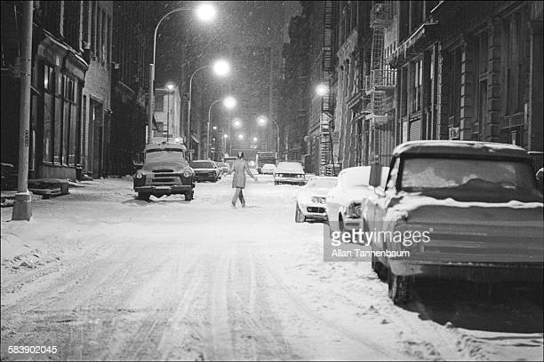 Nighttime view of a pedestrian crossing a snowcovered street in SoHo New York New York February 4 1974