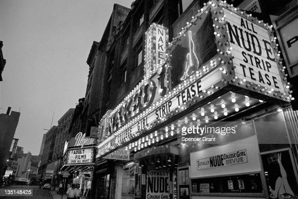 Nighttime view of male passersby walking under the marquee of the 'Naked I' strip club on Washington street in Boston's 'Combat Zone' 1974 Signs for...