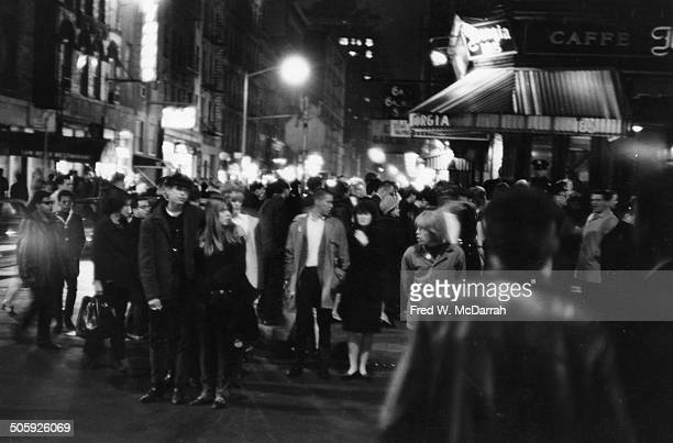 Nighttime view of pedestrians as they cross the intersection of MacDougal and Bleeker streets in Greenwich Village New York New York March 19 1966 At...