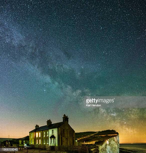 a night-time view of the milky way with coastal cottages in the foreground - stock photo - space and astronomy stock pictures, royalty-free photos & images