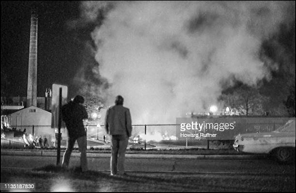 Nighttime view of two Kent State University students as they watch the Reserve Officer Training Corps building as it burns during student protests...