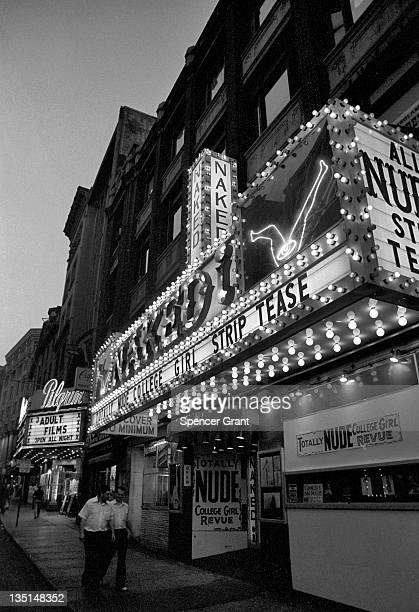 Nighttime view of two male passersby walking under the marquee of the 'Naked I' strip club on Washington street in Boston's 'Combat Zone' 1974 Signs...
