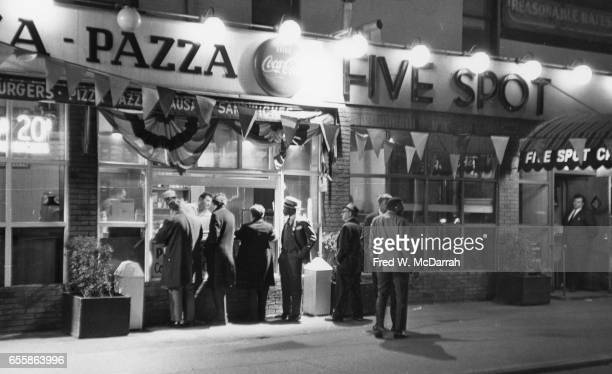 Nighttime view people lined up at the outdoor window of a pizza parlour next door to the Five Spot jazz club New York New York May 14 1966