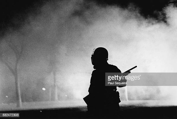 Nighttime view showing a Chicago police officer carrying a shotgun and wearing riot gear silhouetted against tear gas smoke as Lincoln Park is...