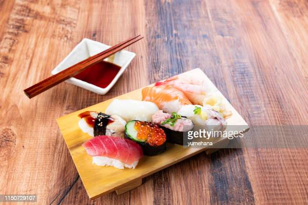 nigiri sushi on wooden board - nigiri stock pictures, royalty-free photos & images