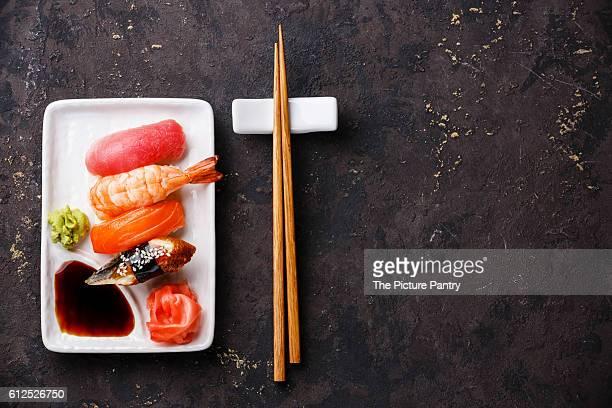 Nigiri sushi set on white plate on dark background