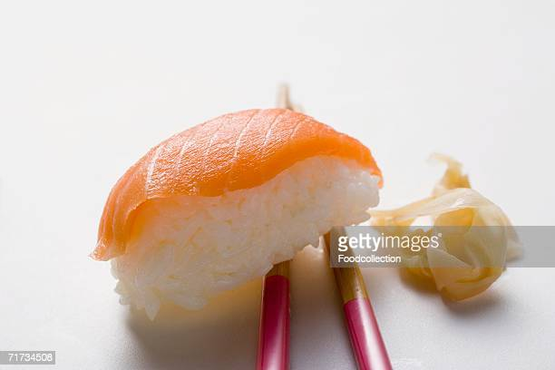 nigiri sushi with salmon on chopsticks and preserved ginger - pickled ginger stock pictures, royalty-free photos & images
