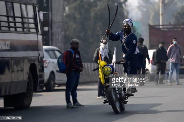 Nihang or a Sikh warrior performs a stunt during a rally in support of protesting farmers against the central government's recent agricultural...