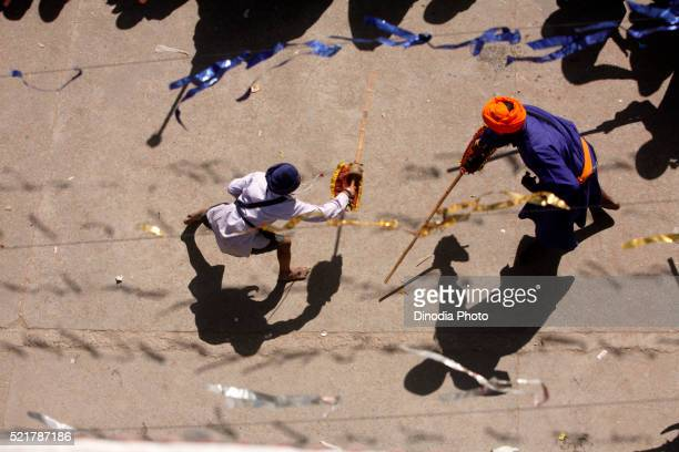 Nihang or Sikh warriors performing stunts with wooden swords in during Hola Mohalla celebrations at Anandpur sahib in Rupnagar
