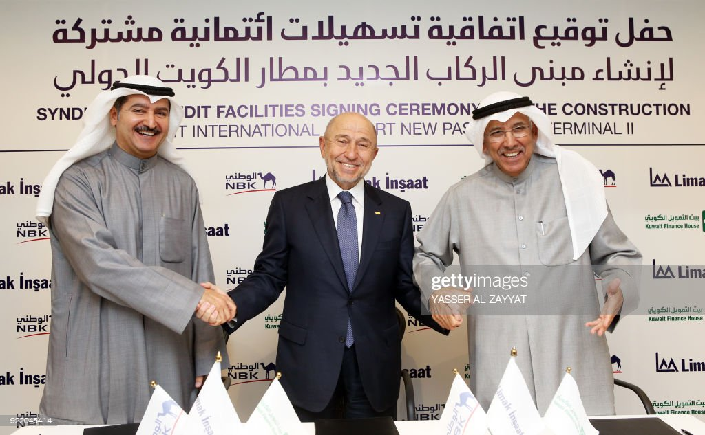 Nihat Ozdemir (C), chairman of Turkish conglomerate Limak Holding AS, poses with Kuwait Finance House bank chairman Hamad al-Marzouk (L) and National Bank of Kuwait chairman Nasser Musaed Al-Sayer (R), during a signing ceremony for a syndicated credit agreement partly financing the construction, completion, furnishing, and maintenance of Kuwait International Airport's second passenger terminal in the capital Kuwait City on February 21, 2018. The new terminal is designed to handle 25 million passengers per year and accommodate all aircraft types through 51 gates and stands. /