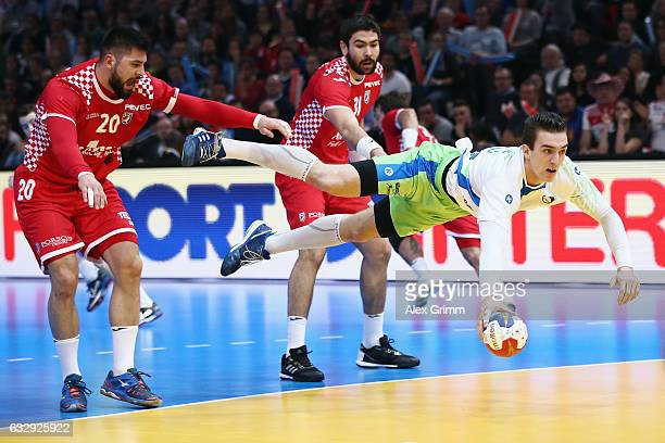 Nik Henigman of Slovenia is challenged by Tin Kontrec of Croatia during the 25th IHF Men's World Championship 2017 Bronze Medal Game between Slovenia...