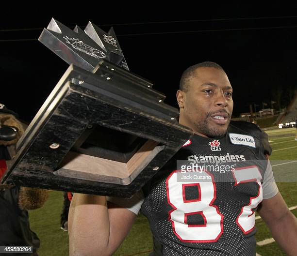 Nik Lewis of the Calgary Stampeders holds up the western trophy with tears in his eyes after Calgary beat the Edmonton Eskimos during the divisional...