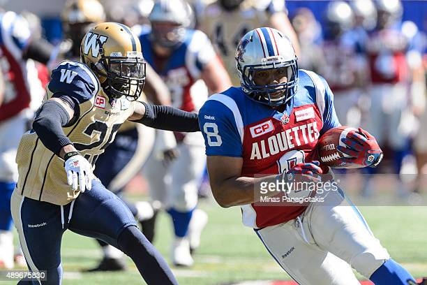 Nik Lewis of the Montreal Alouettes moves the ball past Bruce Johnson of the Winnipeg Blue Bombers during the CFL game at Percival Molson Stadium on...