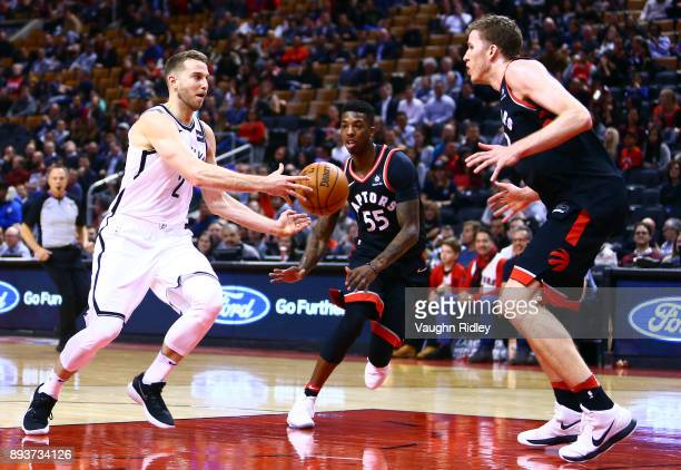 Nik Stauskas of the Brooklyn Nets passes the ball as Delon Wright and Jakob Poeltl of the Toronto Raptors defend during the first half of an NBA game...
