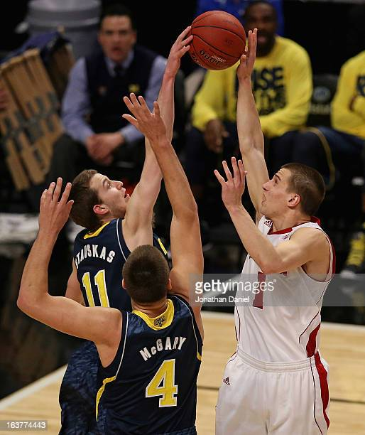 Nik Stauskas of the Michigan Wolverines blocks a shot by Ben Brust of the Wisconsin Badgers while Mitch McGary defends during a quarterfinal game of...