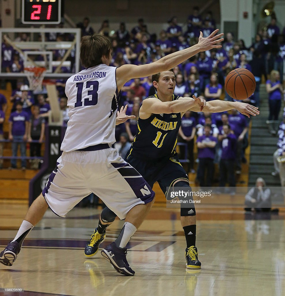 Nik Stauskas #11 of the Michigan Wolverines passes the ball under pressure from Kale Abrahamson #13 of the Northwestern Wildcats at Welsh-Ryan Arena on January 3, 2013 in Evanston, Illinois. Michigan defeated Northwestern 94-66.