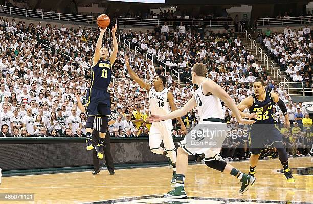 Nik Stauskas of the Michigan Wolverines shoots over Gary Harris of the Michigan State Spartans during the first half of the game at the Breslin...