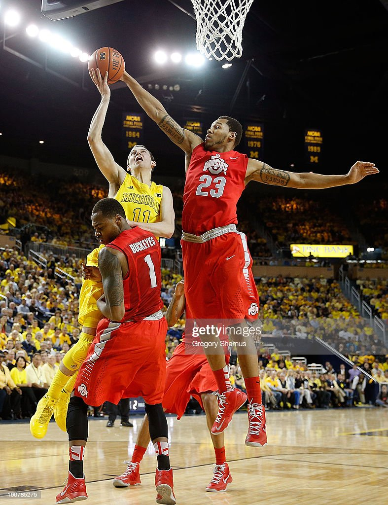 Nik Stauskas #11 of the Michigan Wolverines tries to drive the basket between Amir Williams #23 and Deshaun Thomas #1 of the Ohio State Buckeyes but is called for a charge in the first half at Crisler Center on February 5, 2013 in Ann Arbor, Michigan.