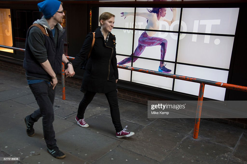 UK - London - Nike advertising runner runs along a barrier near unsuspecting people : News Photo