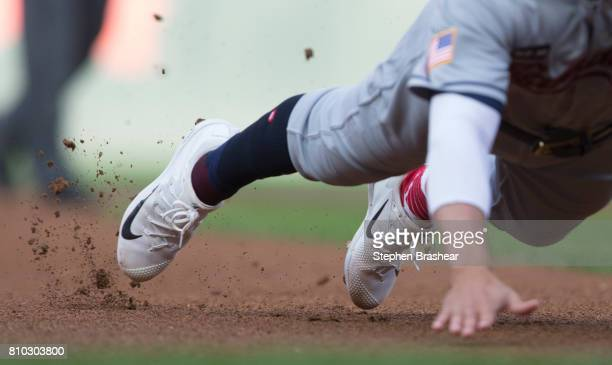Nike baseball cleats kick up dirt as Whit Merrifield of the Kansas City Royals dives into third base during a game against the Seattle Mariners at...
