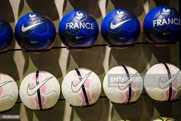 Nike brand Swooshes and French Football Federation Gallic rooster logos sit on a footballs inside the Nike Inc sports apparel store in Paris France...