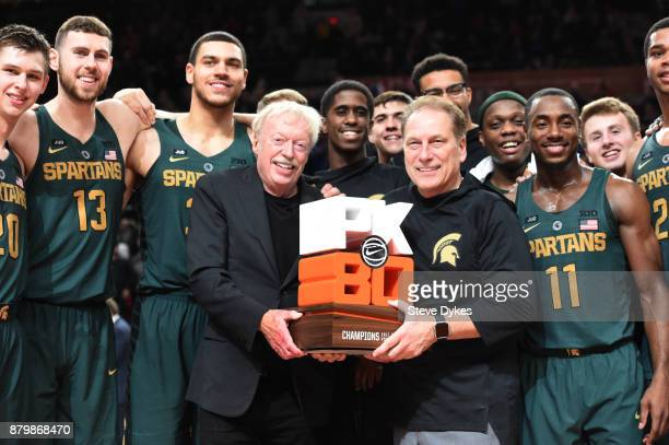 Nike cofounder Phil Knight presents head coach Tom Izzo of the Michigan State Spartans and the Michigan State Spartans the trophy for the 'Victory...