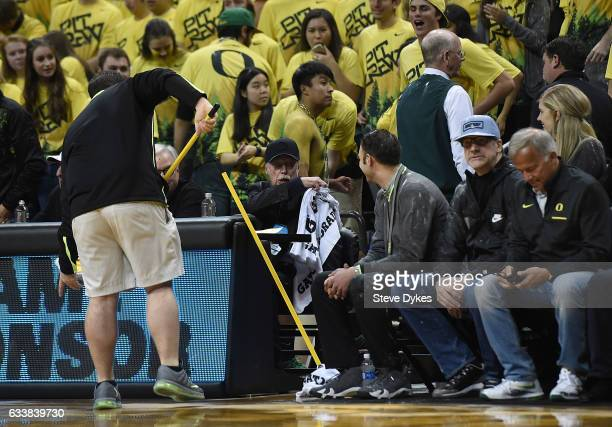 Nike cofounder Phil Knight wipes himself off after a fan or fans threw some sort of powdered substance into the air and onto the court during the...