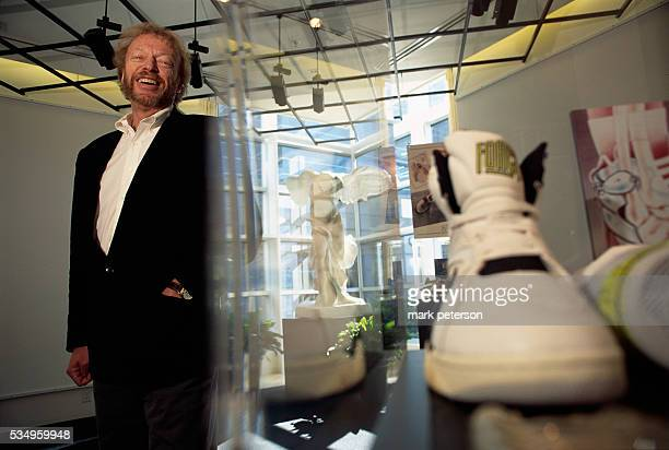 Nike President and CEO Phil Knight standing next to a pair of sneakers on display in a gallery Knight and Nike helped start a sports business...
