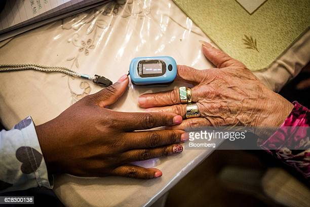 Nikesha McPherson a nurse practitioner for Clover Health uses a pulse oximeter on Margarita Varon at her home in Plainfield New Jersey US on...