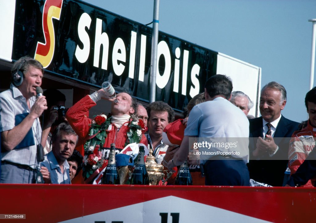 Niki Lauda of Austria (drinking, centre) celebrates winning the British Grand Prix at Brands Hatch, driving a McLaren MP4B with a Ford Cosworth DFV 3.0 V8 engine for Team Marlboro McLaren International, on 18th July 1982. Brands Hatch course commentator Brian Jones can be seen on far left.