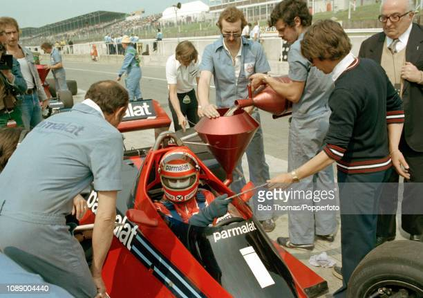 Niki Lauda of Austria in the Brabham BT46 whilst mechanics pour fuel into the car during the British Grand Prix at the Brands Hatch circuit in...