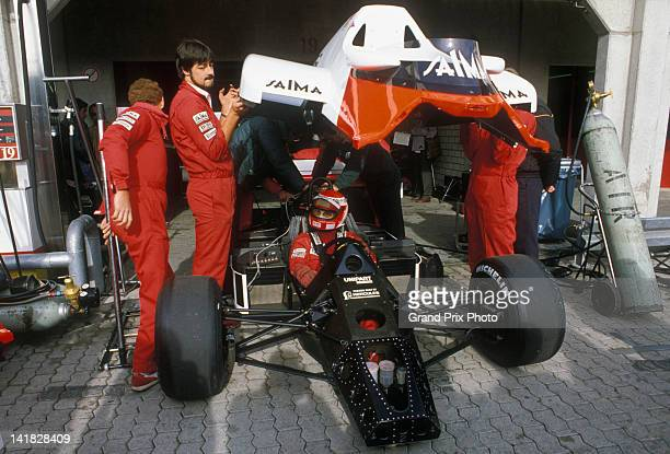 Niki Lauda of Austria sits aboard the Marlboro McLaren International McLaren MP4/2 TAG V6t as the mechanics remove the bodywork in the pits before...