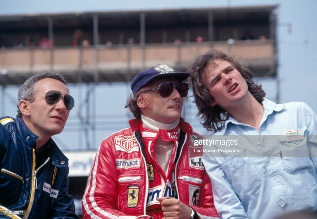 Niki Lauda of Austria (centre) who finished second, driving a Ferrari 312T2 with a Ferrari 015 3.0 F12 engine for Team Scuderia Ferrari SpA SEFAC, talking to British racing motorcyclist Barry Sheene (1950-2003) (right) during the British Grand Prix at Silverstone on 16th July 1977.