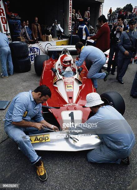 Niki Lauda sits aboard the Scuderia Ferrari 312T2 as mechanics make adjustments to the front wing before the Italian Grand Prix on 12 September 1976...